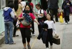 A foreign domestic helper carrying a child walks with another child outside a school in Hong Kong