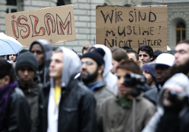 Protesters hold banners reading 'Islam' and 'We are Muslims not Hitler' during a rally against the ban on new minarets in Switzerland in Bern December 12, 2009. Swiss authorities stopped Islamic preacher Pierre Vogel, a German national, at the German border late on Friday to prevent him speaking at a rally in the Swiss capital Berne on Saturday afternoon against a ban on the construction of new minarets, which Switzerland voted for two weeks ago in a referendum.  REUTERS/Ruben Sprich  (SWITZERLAND - Tags: POLITICS RELIGION IMAGES OF THE DAY)